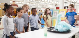 Παιδιά που έχουν τη διασκέδαση που προσέχει ένα πείραμα σε ένα κέντρο επιστήμης στοκ φωτογραφία