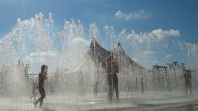 Παιδιά που έχουν τη διασκέδαση στο καλοκαίρι στην έλξη νερού squirt απόθεμα βίντεο