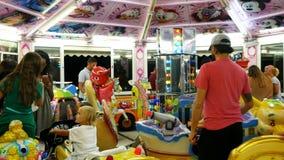 Παιδιά που έχουν το οδηγώντας ιπποδρόμιο διασκέδασης φιλμ μικρού μήκους