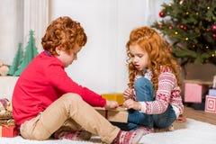 Παιδιά που ανοίγουν το χριστουγεννιάτικο δώρο Στοκ φωτογραφία με δικαίωμα ελεύθερης χρήσης