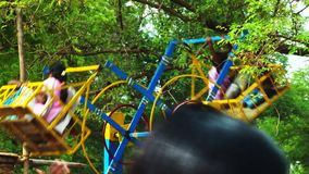 Παιδιά που απολαμβάνουν τη ρόδα στο τοπικό θεματικό πάρκο απόθεμα βίντεο