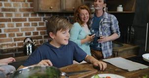 Παιδιά που βοηθούν τους γονείς με το μαγείρεμα του γεύματος, ευτυχής οικογένεια που προετοιμάζει τα τρόφιμα μαζί στην κουζίνα απόθεμα βίντεο