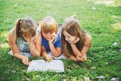 Παιδιά που βρίσκονται στην πράσινη χλόη και που διαβάζουν το βιβλίο ιστορίας Στοκ φωτογραφίες με δικαίωμα ελεύθερης χρήσης