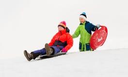 Παιδιά που γλιστρούν στα έλκηθρα κάτω από το λόφο χιονιού το χειμώνα Στοκ φωτογραφία με δικαίωμα ελεύθερης χρήσης