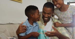 Παιδιά που δίνουν το δώρο στον πατέρα τους στο καθιστικό 4k απόθεμα βίντεο