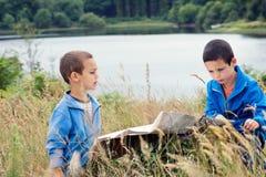 Παιδιά που διαβάζουν έναν χάρτη στη φύση Στοκ εικόνα με δικαίωμα ελεύθερης χρήσης