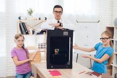 Παιδιά που θέτουν στη κάμερα μαζί με το δάσκαλο και τον τρισδιάστατο εκτυπωτή Στοκ φωτογραφία με δικαίωμα ελεύθερης χρήσης