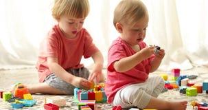 Παιδιά που κάθονται και που παίζουν με το σύνολο ανυψωτών απόθεμα βίντεο