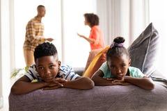 Παιδιά που κάθονται σε έναν καναπέ ενώ οι γονείς τους που υποστηρίζουν στο υπόβαθρο στοκ φωτογραφίες