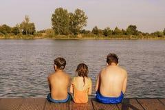 Παιδιά που κάθονται στην αποβάθρα Τρία παιδιά της διαφορετικής ηλικίας - αγόρι εφήβων, στοιχειώδες αγόρι ηλικίας και προσχολική σ Στοκ φωτογραφία με δικαίωμα ελεύθερης χρήσης