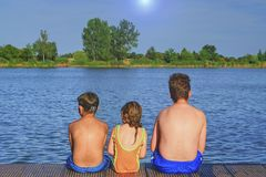 Παιδιά που κάθονται στην αποβάθρα Τρία παιδιά της διαφορετικής ηλικίας - αγόρι εφήβων, στοιχειώδες αγόρι ηλικίας και προσχολική σ Στοκ Εικόνες