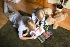 Παιδιά που κάθονται στο πάτωμα και το σχεδιασμό στοκ φωτογραφία με δικαίωμα ελεύθερης χρήσης