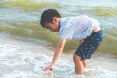 Παιδιά που καθαρίζουν επάνω το πλαστικό μπουκάλι που βρήκε στην παραλία στοκ φωτογραφία