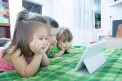 Παιδιά που κοιτάζουν στο μαξιλάρι που βρίσκεται στο κρεβάτι στο σπίτι Χρονικά έξοδα παιδιών Παιδιά που χρησιμοποιούν την ταμπλέτα στοκ φωτογραφία με δικαίωμα ελεύθερης χρήσης