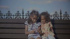 Παιδιά που κουβεντιάζουν on-line χρησιμοποιώντας το έξυπνο τηλέφωνο στον πάγκο απόθεμα βίντεο