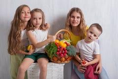 Παιδιά που κρατούν ένα καλάθι των φρέσκων υγιών τροφίμων φρούτων και λαχανικών στοκ φωτογραφία