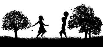 Παιδιά που παίζουν στη σκιαγραφία πάρκων Στοκ Φωτογραφία