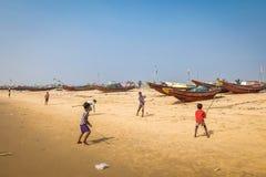 Παιδιά που παίζουν το γρύλο στην αμμώδη παραλία με τα αλιευτικά σκάφη στο υπόβαθρο στοκ φωτογραφία με δικαίωμα ελεύθερης χρήσης