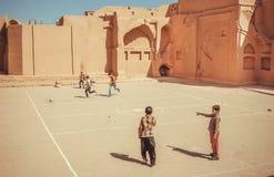 Παιδιά που παίζουν το ποδόσφαιρο στην παιδική χαρά της αρχαίας πόλης αργίλου Περσία Στοκ Εικόνες