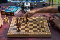 Παιδιά που παίζουν το σκάκι στον κήπο με τα θολωμένα παιχνίδια στο υπόβαθρο στοκ εικόνα
