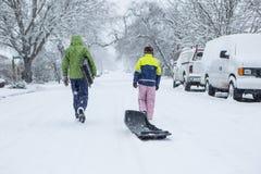 Παιδιά που περπατούν μέσω μιας χιονώδους γειτονιάς με ένα έλκηθρο Στοκ Φωτογραφία