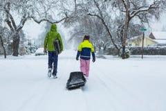 Παιδιά που περπατούν μέσω μιας χιονώδους γειτονιάς με ένα έλκηθρο Στοκ φωτογραφία με δικαίωμα ελεύθερης χρήσης