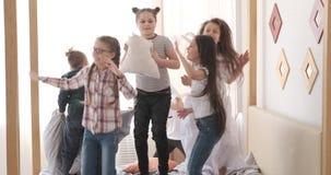 Παιδιά που πηδούν και που έχουν την πάλη μαξιλαριών στο κρεβάτι απόθεμα βίντεο