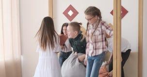 Παιδιά που πηδούν στο κρεβάτι και που έχουν την πάλη μαξιλαριών απόθεμα βίντεο