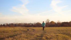 Παιδιά που τρέχουν γύρω από και που παίζουν με το σκυλί σε έναν τομέα φθινοπώρου κάτω από το μπλε ουρανό απόθεμα βίντεο