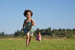 Παιδιά που τρέχουν πέρα από το πεδίο χλόης στοκ φωτογραφία