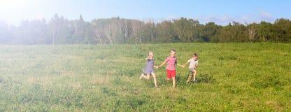 Παιδιά που τρέχουν την άνοιξη τον τομέα, έμβλημα στοκ εικόνες