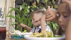 Παιδιά που τρώνε το μεσημεριανό γεύμα στο θερινό εστιατόριο Χαριτωμένα αγόρι και κορίτσι που τρώνε τα υγιή τρόφιμα στο εστιατόριο απόθεμα βίντεο