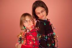 Παιδιά που τυλίγονται επάνω στα φω'τα Χριστουγέννων για τις διακοπές στοκ εικόνες