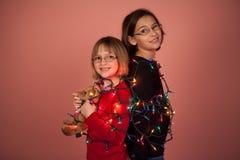 Παιδιά που τυλίγονται επάνω στα φω'τα Χριστουγέννων για τις διακοπές στοκ εικόνα με δικαίωμα ελεύθερης χρήσης