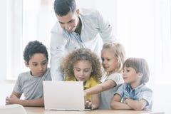 Παιδιά που χρησιμοποιούν Διαδίκτυο κατά τη διάρκεια των κατηγοριών Στοκ φωτογραφία με δικαίωμα ελεύθερης χρήσης