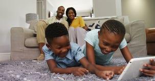 Παιδιά που χρησιμοποιούν την ψηφιακή ταμπλέτα ενώ ζεύγος που χαμογελά στο υπόβαθρο 4k φιλμ μικρού μήκους