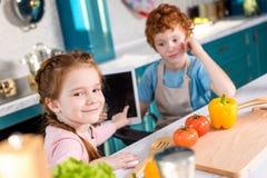 παιδιά που χρησιμοποιούν την ψηφιακή ταμπλέτα μαγειρεύοντας από κοινού Στοκ φωτογραφίες με δικαίωμα ελεύθερης χρήσης