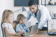 Παιδιά που χρησιμοποιούν το lap-top κατά τη διάρκεια των κατηγοριών Στοκ εικόνες με δικαίωμα ελεύθερης χρήσης