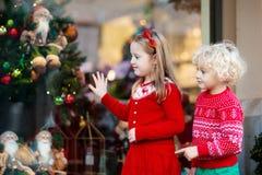 Παιδιά που ψωνίζουν για τα χριστουγεννιάτικα δώρα Τα παιδιά αγοράζουν το decorati Χριστουγέννων στοκ φωτογραφίες