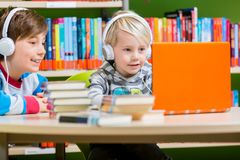 Παιδιά σε μια βιβλιοθήκη που ακούει τα ακουστικά βιβλία στοκ φωτογραφία
