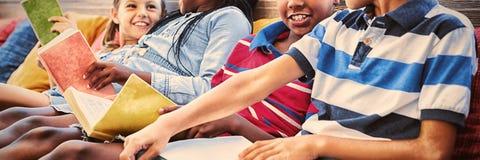 Παιδιά στα βιβλία ανάγνωσης καναπέδων στη βιβλιοθήκη στοκ φωτογραφίες με δικαίωμα ελεύθερης χρήσης