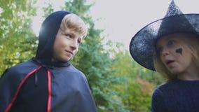 Παιδιά στα κοστούμια αποκριών που συζητούν τις καραμέλες μετά από να τέχνασμα-ή-μεταχειριστεί το γεγονός απόθεμα βίντεο