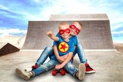 Παιδιά στα κοστούμια superhero που οδηγούν στους απότομους λόφους για να κάνει σκέιτ μπορντ στο πάρκο σαλαχιών ακραίος αθλητισμός στοκ εικόνες
