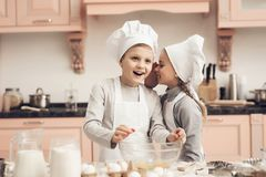 Παιδιά στην κουζίνα Η αδελφή λέει στον αδελφό ένα μυστικό μαγειρεύοντας Στοκ Εικόνες