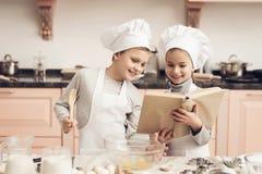 Παιδιά στην κουζίνα Ο αδελφός και η αδελφή διαβάζουν cookbook μαγειρεύοντας Στοκ εικόνα με δικαίωμα ελεύθερης χρήσης