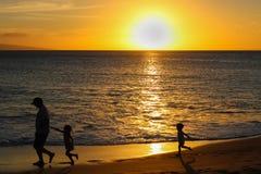 Παιδιά στον πατέρα αυλακώματος σκιαγραφιών στην παραλία στο ηλιοβασίλεμα στοκ εικόνες