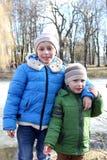 Παιδιά στο πάρκο σε έναν περίπατο στο υπόβαθρο της παγωμένης λίμνης στοκ φωτογραφία με δικαίωμα ελεύθερης χρήσης