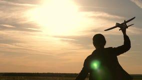 Παιδιά στο υπόβαθρο του ήλιου με ένα αεροπλάνο διαθέσιμο παιχνίδι κοριτσιών με ένα αεροπλάνο παιχνιδιών στο ηλιοβασίλεμα Όνειρα τ απόθεμα βίντεο