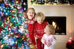 Παιδιά στο χριστουγεννιάτικο δέντρο Παιδιά στην εστία στην παραμονή Χριστουγέννων στοκ εικόνες με δικαίωμα ελεύθερης χρήσης
