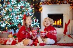 Παιδιά στο χριστουγεννιάτικο δέντρο Τα παιδιά πίνουν το καυτό κακάο στοκ φωτογραφία